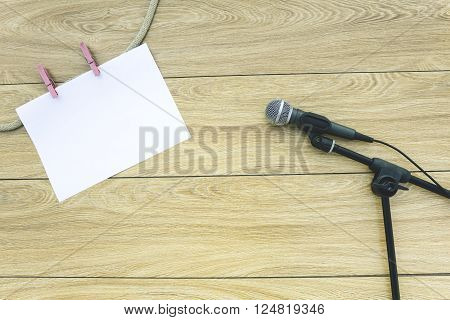 Microphone on the stand and a sheet of paper on clothespins on a wooden background