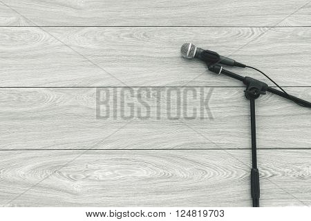 A microphone on the stand on a wooden background, black and white photo