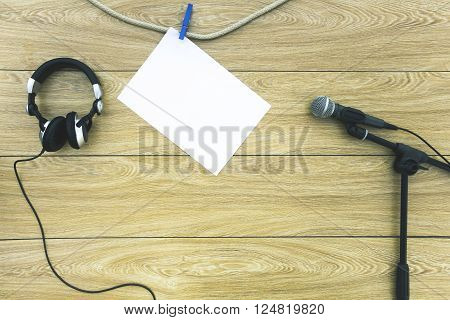 Microphone on the stand, headphones and a sheet of paper on a clothespin on a wooden background