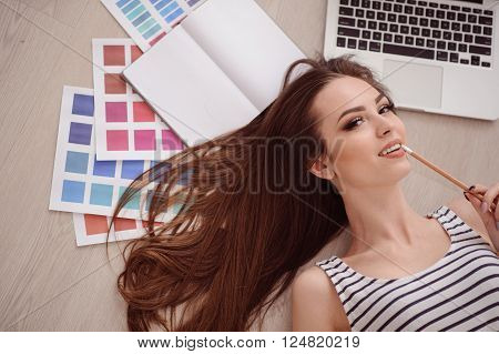 Charming glance. Cheerful seducing positive girl holding pencil and looking at you while lying on the floor
