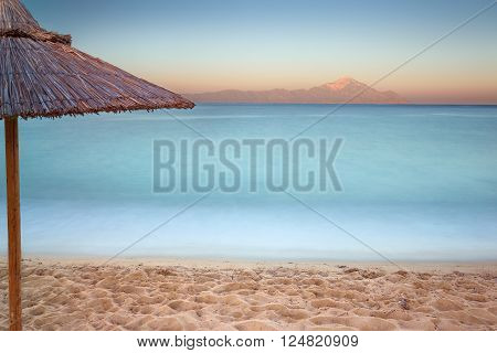 Beautiful sunset on Greek coast of Aegean sea with holy mountain Athos in background. Long exposure shot with motion blur effect. Chalkidiki Greece.