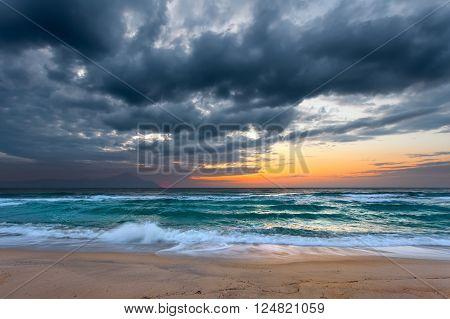 Beautiful dawn on Greek coast of Aegean sea with holy mountain Athos in background. Chalkidiki, Greece.