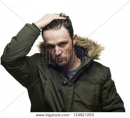 High key studio portrait of young adult caucasian model wearing winter coat with hood