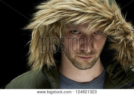 Low key studio portrait of suspicious young adult caucasian model wearing winter coat with hood on.