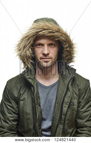 High key studio portrait of young adult caucasian model wearing winter coat with hood on staring into camera. Isolated on white.