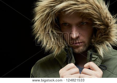 Low key studio portrait of young adult caucasian model wearing winter coat with hood on.