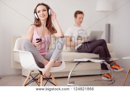 Reveal stress. Cheerful beautiful positive girl holding cellphone and listening to music with her boyfriend using laptop in the background