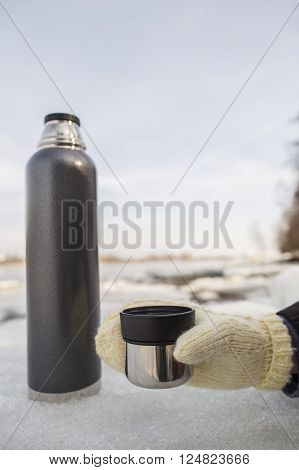 Man holding a cup of hot tea from a thermos in hand on a wearing mitten on the banks of the river in the spring sunny day