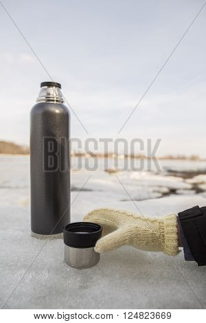 A man takes a hand in mitten cup of hot tea from a thermos, which stands on an ice floe on the river a sunny day
