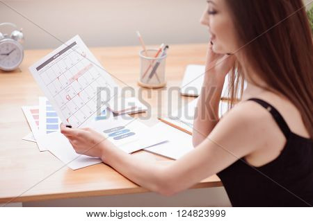 Mind the deadlines. Pleasant content charming girl talking on cell phone and holding calendar while working at the table