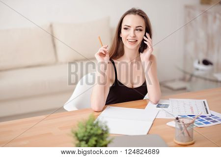 Nice interlocutor. Cheerful content positive beautiful girl sitting at the table and talking on mobile phone while being involved in work