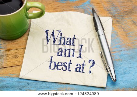 What am I best at? Handwriting on a napkin with cup of coffee against gray slate stone background