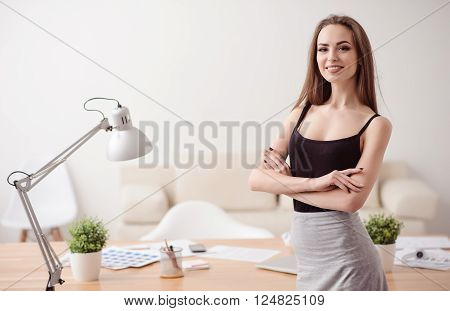 Confidence in mind. Positive beautiful woman folding her hands and smiling while working in the office