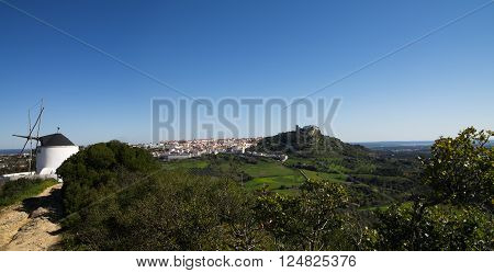 Panorama showing a white wind mill and Palmela town in background with its castle on top of the hill. Blue clear sky. Setubal Portugal.