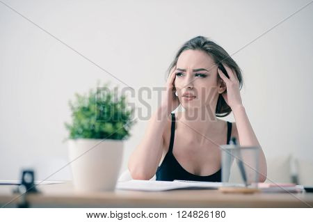 Many tasks to do. Tired pleasant attractive woman touching her head and feeling tired while sitting at  the table