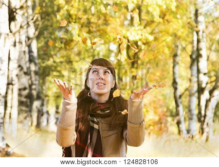 Beautiful girl in autumn park catch hands falling leaves