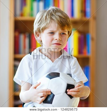 Little blond preschool kid boy with ball watching soccer european cup game on tv. Sad crying child about lost game of his football team. Champions league concept.