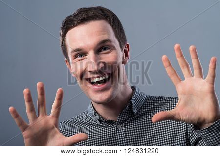 Full of gladness. Cheerful content handsome man smiling and holding her palms in front of the face while expressing joy
