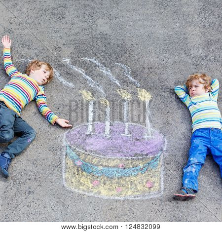 Two happy little kids having fun with big birthday cake picture drawing with colorful chalks. Creative leisure for children outdoors in summer. Kids blowing candles.