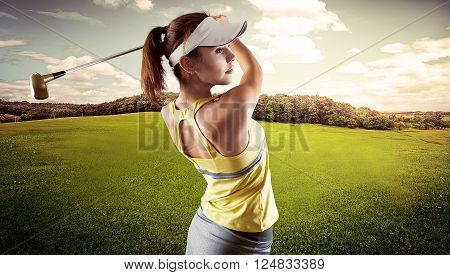 Energetic woman practicing golf exercise over beautiful landscape background. Pretty sportswoman hitting the ball with golf club.