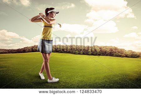Woman golf player preparing to hit the ball. Young active female looking at ball course on green field.