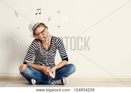 Woman listening music in earphones with sheet music on the wall