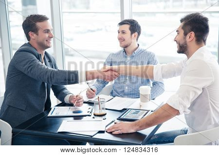 Deal. Positive Delighted positive handsome colleagues sitting at the table and shaking hands while discussing the project