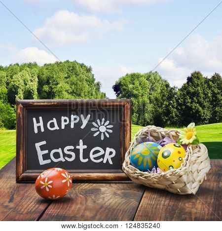 Painted Easter eggs in a basket on the table with a congratulatory text