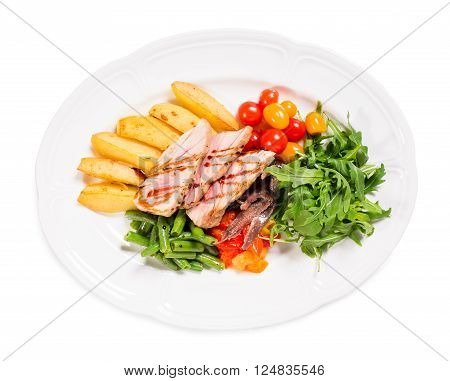 Delicious grilled tuna salad with baked potatoes and french beans. Isolated on a white background.