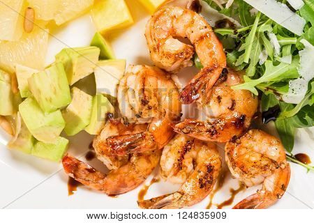 Jumbo shrimp salad with avocado mango topped with pine nuts and parmesan cheese. Macro. Photo can be used as a whole background.