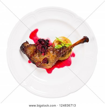 Delicious duck leg confit with red berry sauce and baked sliced apple covered with cinnamon as a garnish. Isolated on a white background.