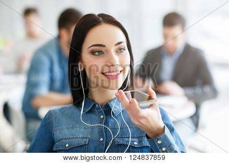 Nice to hear you. Cheerful  content beautiful smiling girl holding cell phone and talking on it while expressing joy