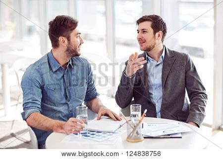 Bright ideas inside. Cheerful handsome positive male colleagues sitting at the table and discussing project while feeling delighted