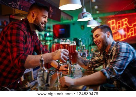 Happy barman and his friend clinking with glasses of beer