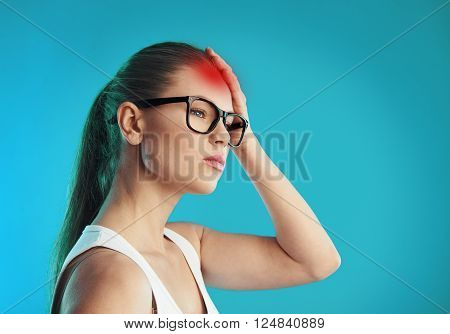 Young sad woman in eyeglasses having headache. Concept of hangover, stress and disease.