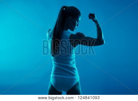 Portrait of young athletic woman massaging her sore arm. Bone fracture concept.