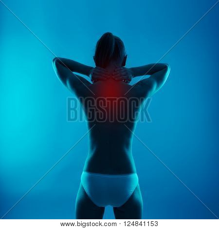 Lumbago problem. Young female massaging her sore back. Health care and medicine.