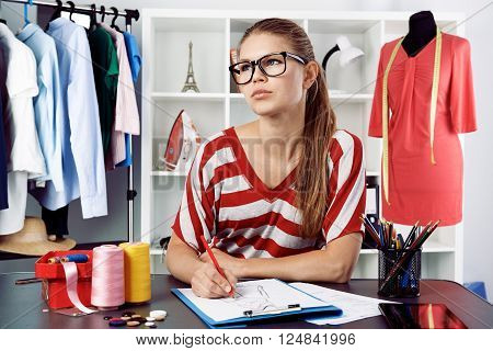 Clothing stylist thinking of new fashion dress design drawing template at the desk. Young successful female atelier owner creating trendy clothes.