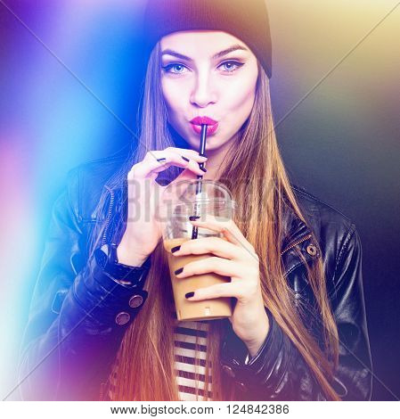 Cool blonde teenage girl in black drinking takeaway coffee from plastic cup with straw.