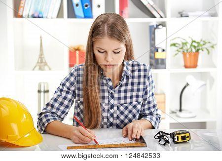 Woman engineer working over urban design project sitting at the table with angle, pencil and helmet.