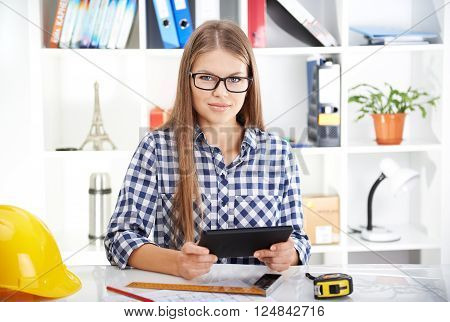 Cheerful woman with tablet pc sitting at the desk in engineer's office. Young woman studying CAD.