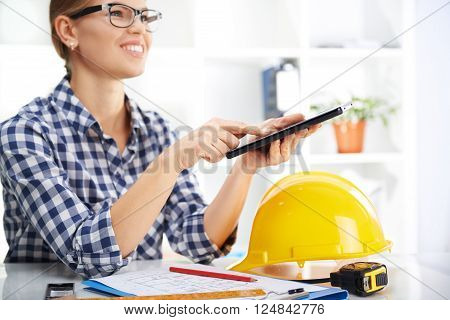 Portrait of smiling woman architect holding tablet pc and pointing something. Young woman designer working in the office.