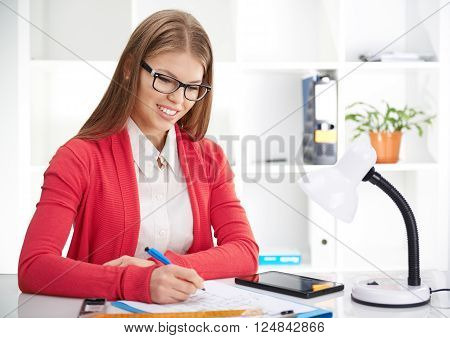 Pretty smiling woman designer drawing on paper and using digital tablet in the office. Female architect estimating construction plan.