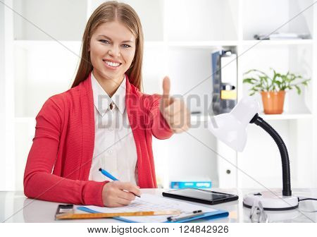 Portrait of attractive female designer drawing blueprint and talking on mobile phone. Young female engineer working on new construction project in the office.