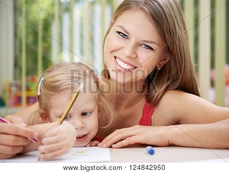 Close up portrait of cheerful mother teaching her little daughter at home. Concept of daycare, kindergarten and education.
