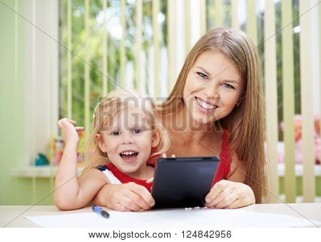 Portrait of happy family reading e-book sitting at the table in playroom. Concept of child education and development.