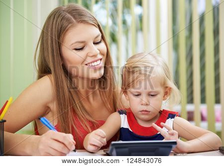Young family calculating domestic savings. Attractive female with small daughter sitting at the table at home.
