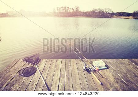 Vintage toned fishing equipment on a wooden pier at sunset.