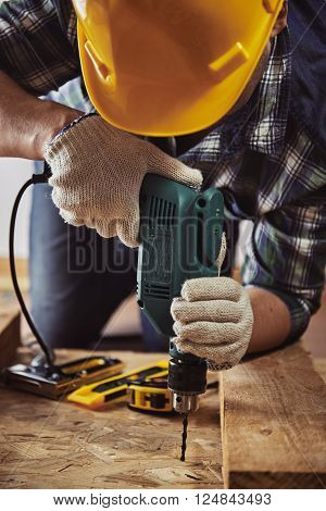 Craftsman in helmet and gloves holding drill at work. Male contractor woodworking with building tools.