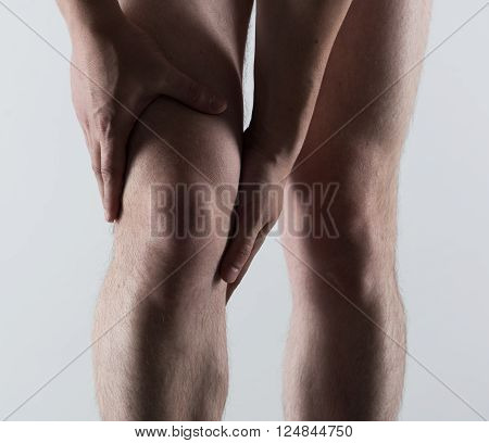 Knee spasm or injury. Young man touching his sore leg.